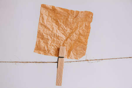 Brown stickers on clothesline with wooden clothespin isolated on white background. Place for your text Фото со стока