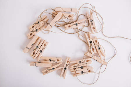 Wooden clothespins with rope on white background. View from above. Place for your text