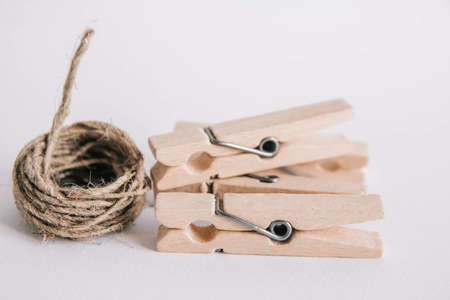 Wooden clothespins with rope on white background. Place for your text Фото со стока