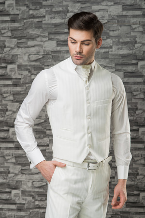 Man model in white waistcoat, trousers, shirt and cravat holding