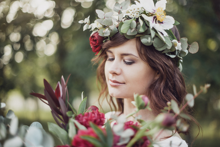 Portrait of young beautiful girl with flowers in circlet of flowers Stock Photo