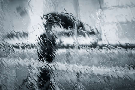 A blurry woman silhouette under the rain with umbrella through wet window. Black and white