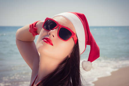 enjoing: Portrait of a happy young woman in Santa Claus hat enjoing her Christmas vacation on a sunny beach