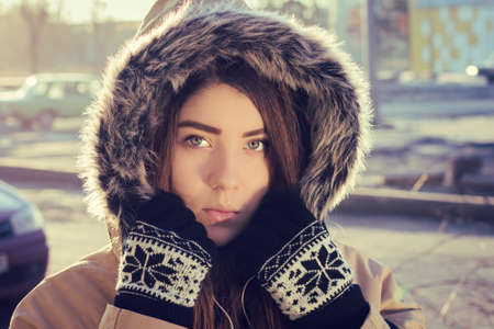 fur hood: Portrait close up  of a teenage girl outdoor wearing gloves and winter coat with the faux - fur hood on. Toned effect