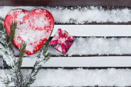 pinetree: A gift box with red heart shaped tin box and a fragment of a pine-tree branch on a bench covered with snow. Valentines day theme Stock Photo