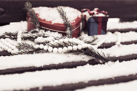 pinetree: White pearl necklace, red heart shaped tin box with a gift box and a fragment of a pine-tree branch on a bench covered with snow. Valentines day theme. Toned effect