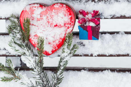 pinetree: Red heart shaped tin box with a gift box and a fragment of a pine-tree branch on a bench covered with snow. Valentines day theme