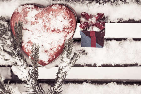 pinetree: Red heart shaped tin box with a gift box and a fragment of a pine-tree branch on a bench covered with snow. Valentines day theme. Toned effect