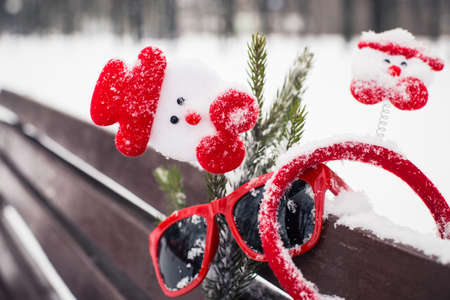 pinetree: Funny winter composition with christmas accessories, red sunglasses and a fragment of a pine-tree branch on a bench covered with snow