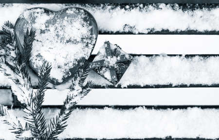 pinetree: A gift box with red heart shaped tin box and a fragment of a pine-tree branch on a bench covered with snow. Black and white. Valentines day theme Stock Photo