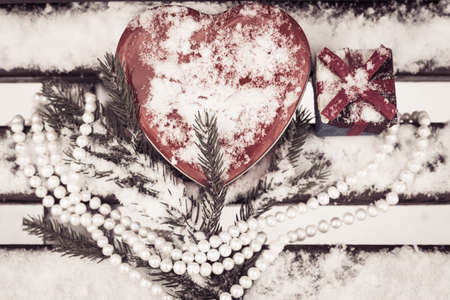 pinetree: Red heart shaped tin box and a gift box with a white pearl necklace and a fragment of a pine-tree branch on a bench covered with snow. Valentines day theme. Toned effect