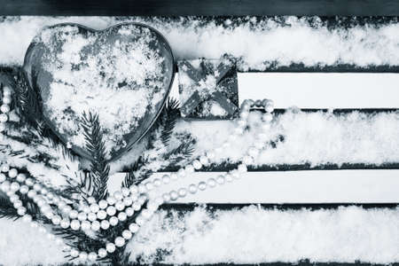 pinetree: A gift box, red heart shaped tin box with a white pearl necklace and a fragment of a pine-tree branch on a bench covered with snow. Valentines day theme. Black and white