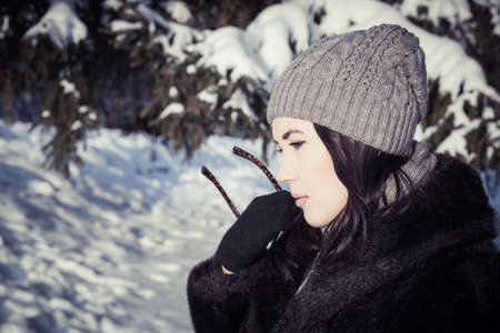 beautiful sad: Portrait in profile of a pretty thoughtful young woman walking on a sunny winter day in snow-covered park. Toned effect Stock Photo