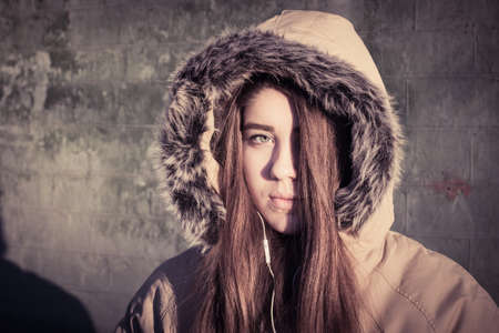 fur hood: Portrait close up of a teenage girl outdoor wearing winter coat with the faux - fur hood on. Toned effect