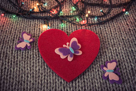 woollen: Red felt heart with colorful butterflies, colorful garland with woollen texture in the background. Valentines  theme