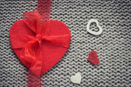 woollen: Red felt heart and  colorful decorative  hearts with woollen texture in the background. Valentines  theme