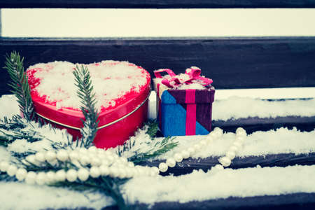 pinetree: A gift box, white pearl necklace, red heart shaped tin box with a fragment of a pine-tree branch on a bench covered with snow. Valentines day theme. Toned effect