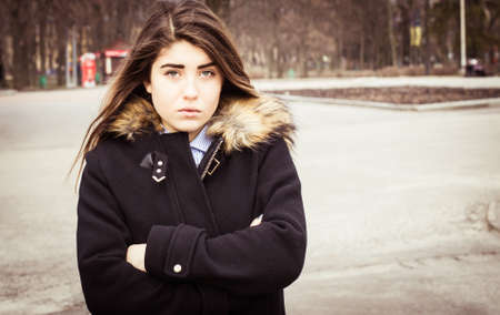 Outdoor portrait of a thoughtful teenage girl wearing a black coat.