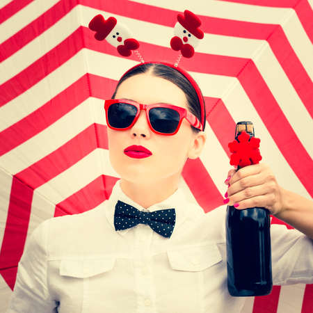 Portrait of a pretty girl in Christmas outfit with a bottle of champagne next to a striped background Stock Photo