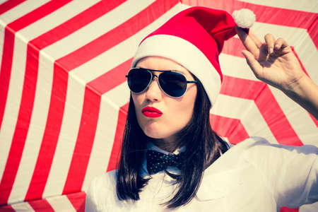 Portrait of a pretty girl in Santa Claus hat and  sunglasses with bright painted lips next to a striped background Stock Photo