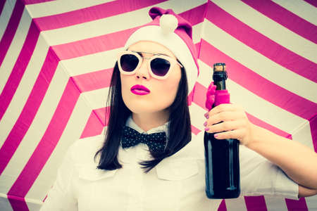 Portrait of a pretty girl in Christmas outfit with a bottle of champagne next to a striped background. Toned effect