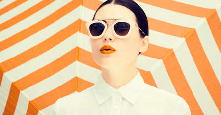 Fashion portrait of a beautiful girl with bright painted lips and sunglasses next to a striped background