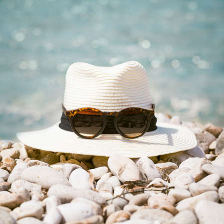 Summer compositions with womans hat and sunglasses on the beach