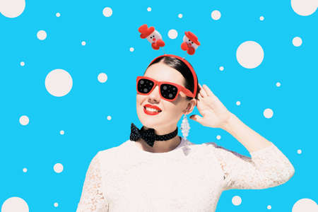 Portrait of a pretty woman in christmas outfit and sunglasses with bright painted lips on a colorful background 스톡 콘텐츠