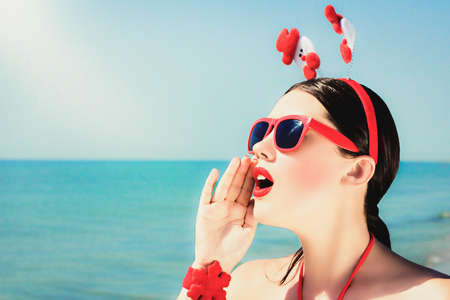 Outdoor close up portrait  of a pretty young woman calling out in christmas themed outfit and sunglasses on a beach. Holiday vacation theme concept Stock Photo