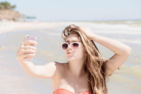 Portrait of a pretty teenage girl with long hair and sunglasses taking self portrait with her smartphone and enjoying her time on the beach