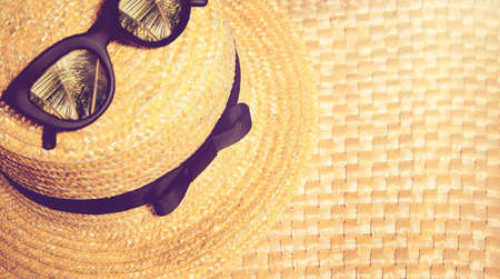 Straw hat with black trendy sunglasses with reflection of palms in them on a straw bag. Beach summer vacation theme concept.