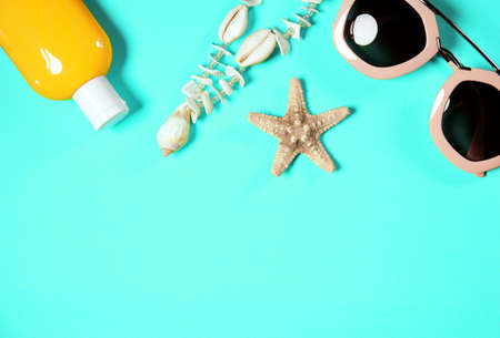 Beach accessories on a bright green colorful background. Dried starfish, shells necklace, a bottle of sunscreen lotion and  sunglasses . Summer vacation background.Image is with copy space Standard-Bild