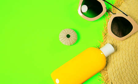 Beach accessories on a bright green colorful background. Trendy pink sunglasses, a bottle of sunscreen lotion, a fragment of a straw hat and sea urchin shell . Summer vacation background. Top view image with copy space Imagens