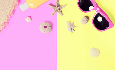 Trendy fashion beach accessories on a bright colorful background. Dried starfish, shells, a bottle of sunscreen lotion, a fragment of a straw hat and sunglasses . Summer vacation background.