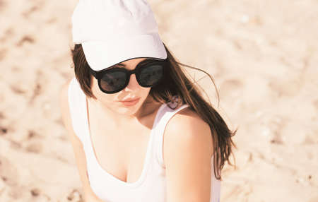 Portrait of a pretty teenage girl with long hair wearing white baseball cap, white swimsuit and trendy sunglasses sitting on the sand and enjoying her time on the beach 스톡 콘텐츠