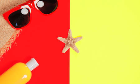 Trendy fashion beach accessories on a bright colorful background. Sunglasses, fragment of a straw hat, a bottle of sunscreen lotion, dried starfish and shells. Summer vacation background.