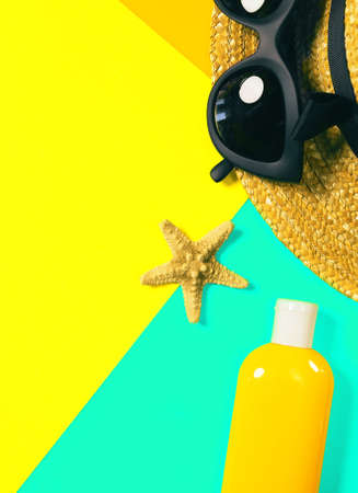 Beach accessories on a bright colorful background. A bottle of sunscreen lotion, dried starfish, a fragment of a straw hat and trendy black sunglasses . Summer vacation background. Image is with copy space Imagens