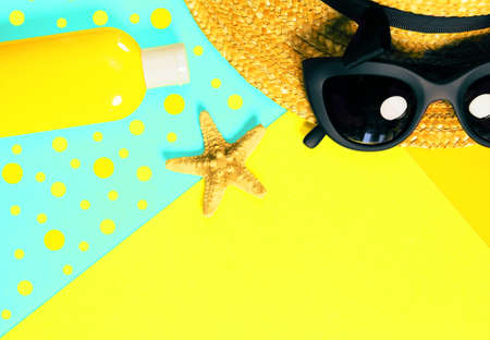 Beach accessories on a bright colorful background. A bottle of sunscreen lotion, dried starfish, a fragment of a straw hat and trendy black sunglasses . Imagens