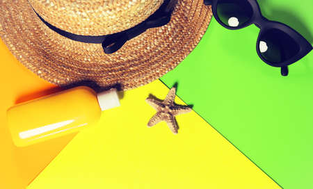 Beach accessories on a bright colorful background. A fragment of a straw hat, dried starfish, a bottle of sunscreen lotion and black trendy sunglasses . Imagens