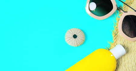 Beach accessories on a bright green colorful background. Trendy pink sunglasses, a bottle of sunscreen lotion, a fragment of a straw hat and sea urchin shell .