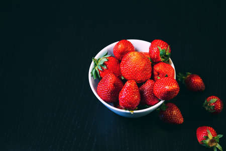 White bowl with fresh red strawberries on a dark wooden table close up. Spring or summer backgruond. Healthy food ingredients theme concept. Image is with copy space.