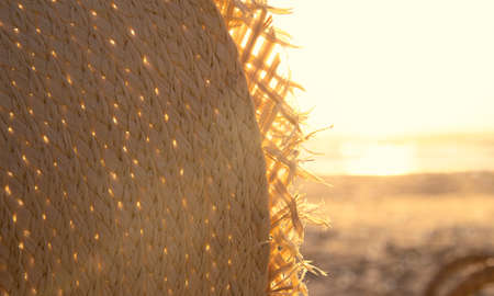 Fragment of a straw hat in sunset light on the beach. Vacation theme concept. Summer holiday background