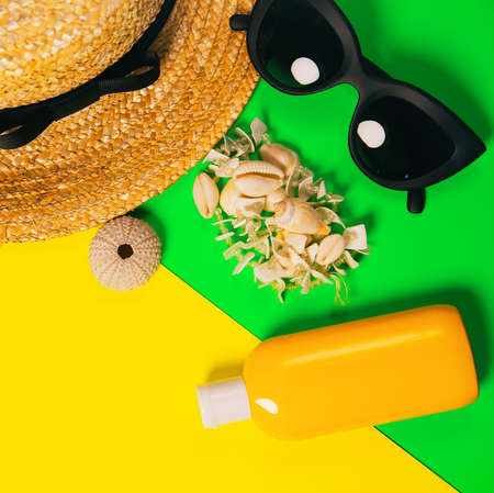 Beach accessories on a bright neon colorful background. A fragment of a straw hat and sea urchin shell , shells necklace, a bottle of sunscreen lotion and  sunglasses . Summer vacation background. Imagens