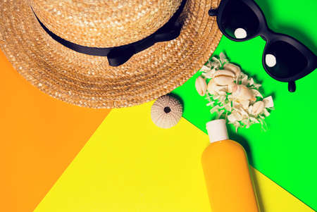 Beach accessories on a bright neon colorful background. A fragment of a straw hat and sea urchin shell , shells necklace, a bottle of sunscreen lotion and  sunglasses .