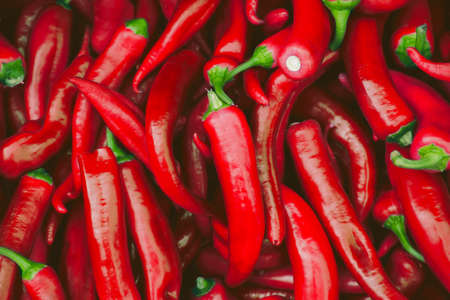 Fresh hot green chilli pepppers in the market as a background. Spicy food ingredient Imagens