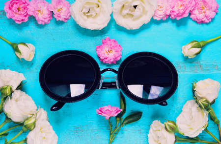 Trandy fashion sunglasses and fresh garden roses on an old painted wooden table. Summer background concept. Top view.