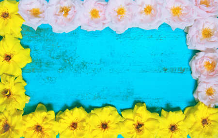 Old painted wooden table  with fresh yellow and pink garden roses lying as a frame. Summer background with copy space for posters, seasonal cards, blogs and web design. Top view Stock Photo