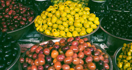 Olives in bowls at the market for sale. Traditional mediterranean food suitable for vegans and vegetarians. Stock fotó