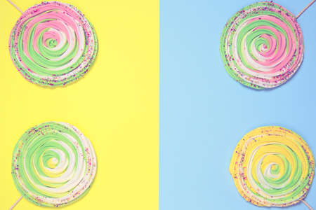 Colorful meringues on stick on colorful background. Festive and party concept. Minimal style. Flat lay. Top view