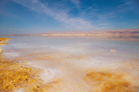 Beautiful view of salty Dead Sea shore with clear water and blue sky. Ein Bokek, Israel. Scenery background for posters, blogs, web design